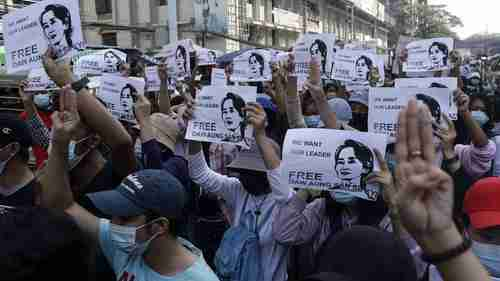 Thousands of protesters in Yangon on Sunday carrying placards with image of Aung San Suu Kyi (BBC)