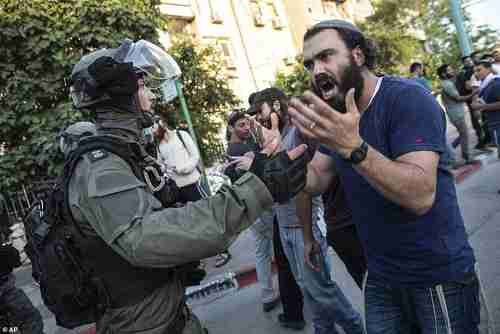 Israeli riot policeman tries to block a Jewish right-wing man as communal violence erupted in Lod on Wednesday (AP)