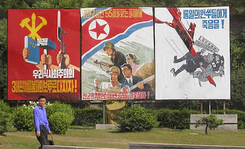 Prominent billboard in Pyongyang, North Korea, 2003.  The right-most frame shows a North Korean spearing an American with a bayonet.