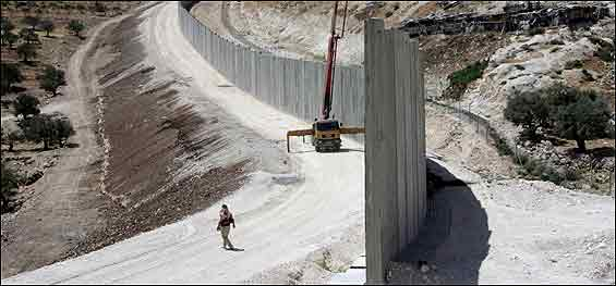A Palestinian walks by the security fence.  <font size=-2>(Source: AFP)</font>
