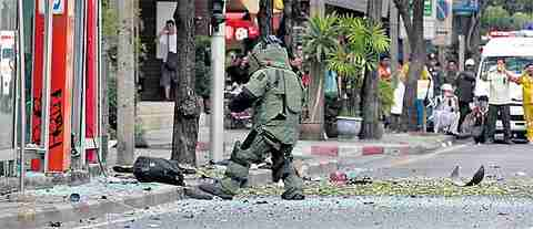 Bystanders watch as a bomb disposal expert approaches the attack site in Bangkok