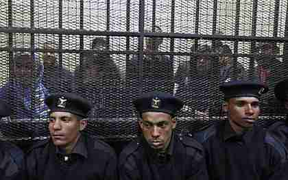 Policemen sit in front of a cage holding Egyptian employees of pro-democracy groups on trial (AP)