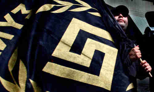 The Golden Dawn symbol appears on a flag held by a party member ...