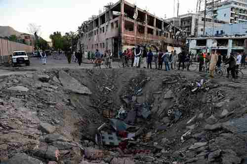 Afghan security forces and residents stand near the 13ft deep crater left by Wednesday's truck bomb attack in Kabul (AFP)