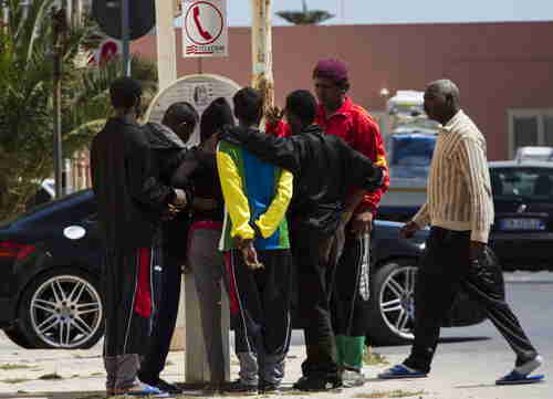 Migrants queue at phone booth on the Island of Lampedusa, Southern Italy, on Thursday (AP)