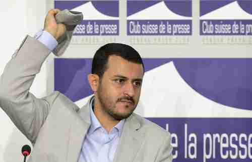 Hamza al-Houthi throws back a shoe thrown at him on Thursday (AFP)
