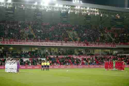 Greece's players, left, and Turkey's players, right, bow and observe a minute of silence to honor the victims of the Paris attacks on Wednesday (AP)