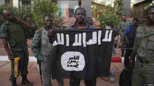 Mali security officers show a jihadist flag that belonged to the hotel attackers (Reuters)