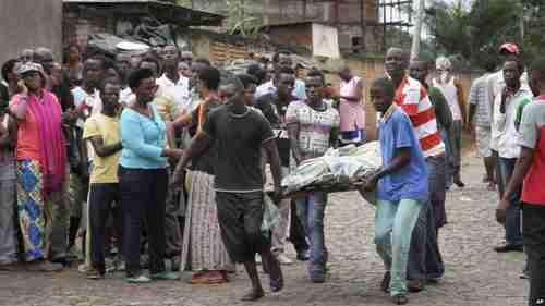 Men carry away a dead body in Bujumbura on Saturday (VOA)