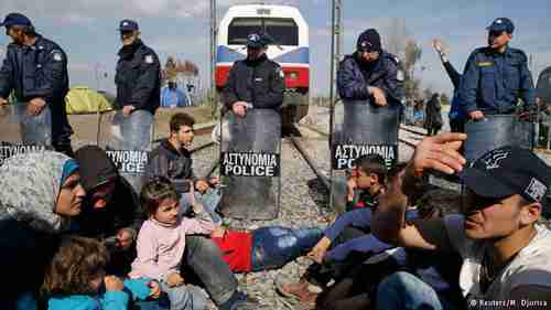 Migrants block the railway track at the Greek-Macedonian border (Reuters)