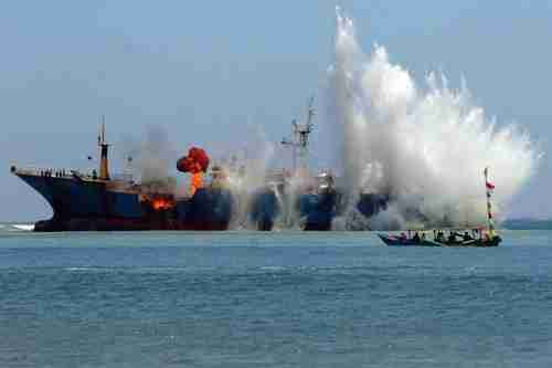 Indonesians blow up a foreign fishing boat caught illegally fishing in Indonesian waters (EPA)