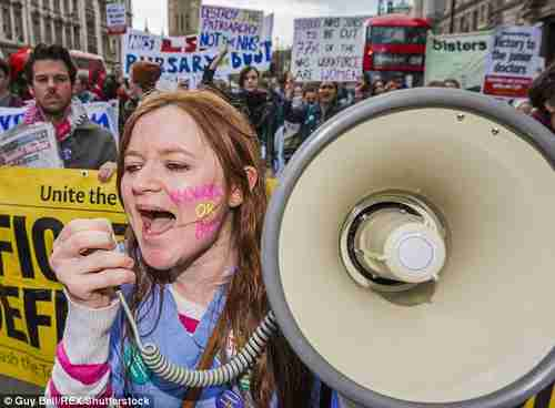 Striking protesters carry signs saying 'Destroy the patriarchy, not the NHS' and 'Victory to the junior doctors' (Press Association)