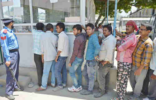 Saudi migrant workers at a bus stop in Kashmir on Wednesday (AFP)