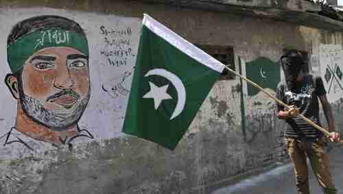 A masked Kashmir protester in Kashmir on Sunday waves a Pakistan flag next to a graffiti of Hizbul Mujahideen commander Burhan Muzaffar Wani. Wani was shot and killed by police on July 8, triggering weeks of riots, demonstrations and violence since then. (Hindustan Times)
