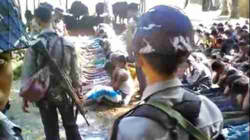 Screen grab from video. Dozens of Rohingyas on the right are being forced to watch the beating