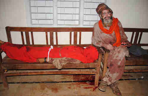 A Pakistani covered with blood sits with the body of a blast victim on Thursday (AFP)